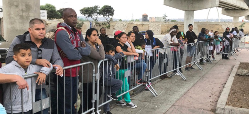 Asylum seekers in Tijuana, Mexico, listen to names being called from a waiting list to claim asylum at a border crossing in San Diego.