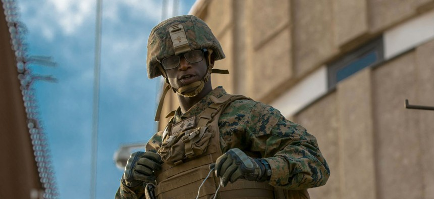 U.S. Marine Corps Lance Cpl. Jente Brothers, assigned to Special Purpose Marine Air-Ground Task Force 7, stands on a forklift that is being used to fortify fencing along the Calexico West Port of Entry in Calexico, California on Nov. 17, 2018.