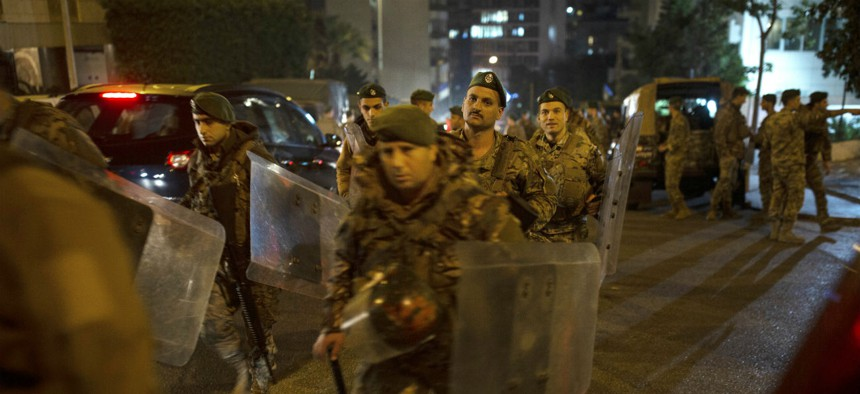 Lebanese security forces move into position outside of the home of newly-assigned Lebanese Prime Minister, Hassan Diab, following his meeting with Lebanese President Michel Aoun in Beirut, Lebanon, Thursday, Dec. 19, 2019.