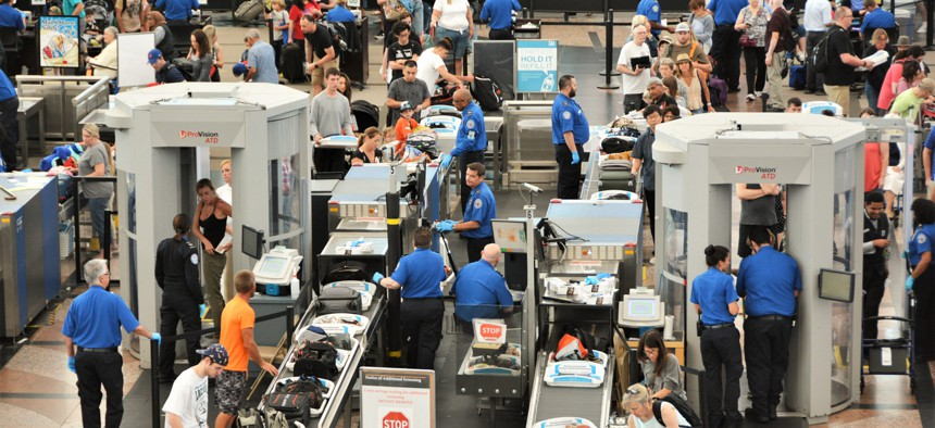 Although Transportation Security Administration screeners, shown here processing passengers at the Denver International Airport in July 2019, are eligible for new parental leave benefits for federal employees, many of their colleagues are not.