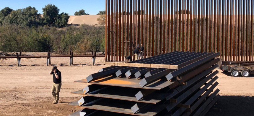 People work on a portion of border wall which was under construction in January in Yuma, Ariz.