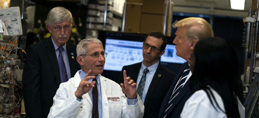 Dr. Anthony Fauci, director of the National Institute of Allergy and Infectious Diseases, talks with President Donald Trump during a tour of the Viral Pathogenesis Laboratory at the National Institutes of Health, Tuesday, March 3, 2020, in Bethesda, Md.