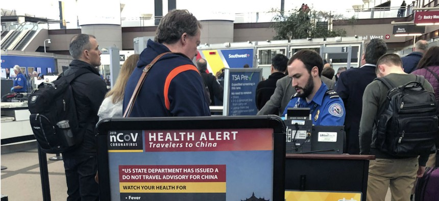 A health alert for people traveling to China is shown at a TSA security checkpoint at the Denver International Airport. Many federal employees and contractors face exposure to the novel coronavirus in the course of their work.