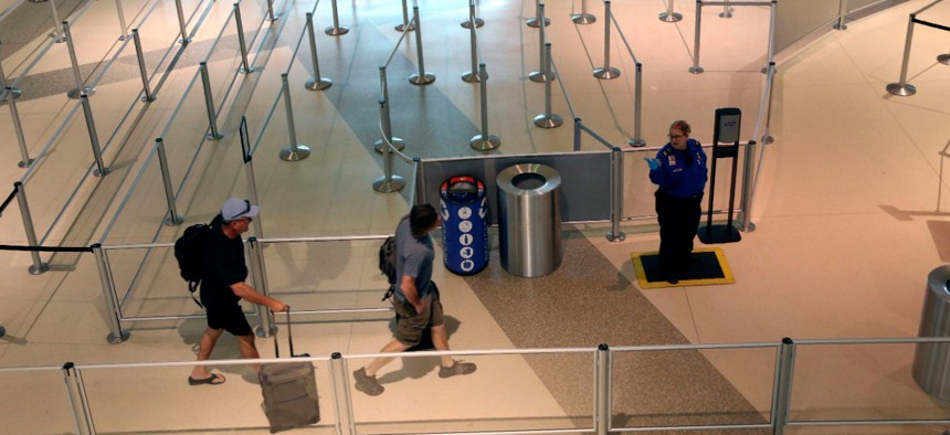 A TSA agent speaks to travelers passing through an empty security queue at Love Field airport in Dallas on Thursday, amid concerns related to the coronavirus pandemic.