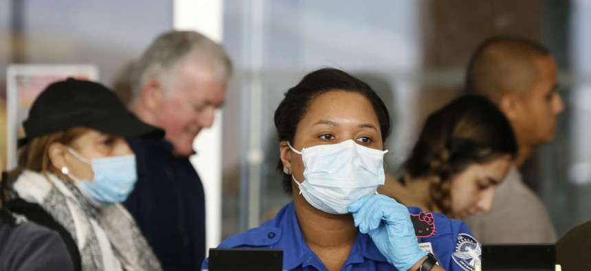 A TSA employee adjusts her face mask while screening passengers entering through a checkpoint at John F. Kennedy International Airport on March 14, 2020, in New York.