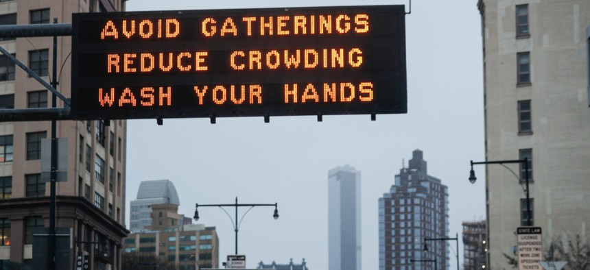 Messages on how to reduce the spread of COVID-19, the disease caused by the new coronavirus, are displayed at the mouth of the Manhattan Bridge on Monday.