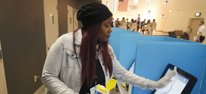 Denise Arnold, an early voting election official with the Chicago Board of Elections sanitizes a voting machine on March 14 during early voting for the Illinois primary.