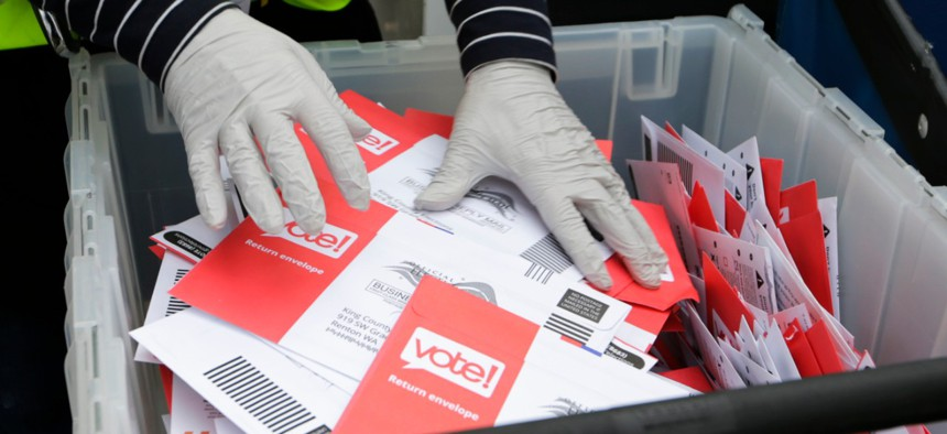 Wearing gloves, a King County Election worker collect ballots from a drop box in the Washington State primary in Seattle on March 10.