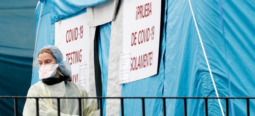 A medical worker prepares to reenter a COVID-19 testing tent set up outside Elmhurst Hospital Center in New York on March 28.