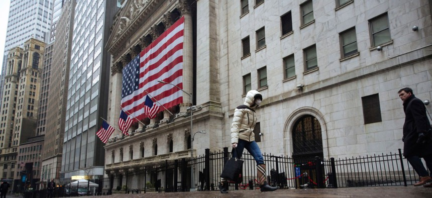 A pedestrian wearing a surgical mask and gloves walks past the New York Stock Exchange in mid-March.