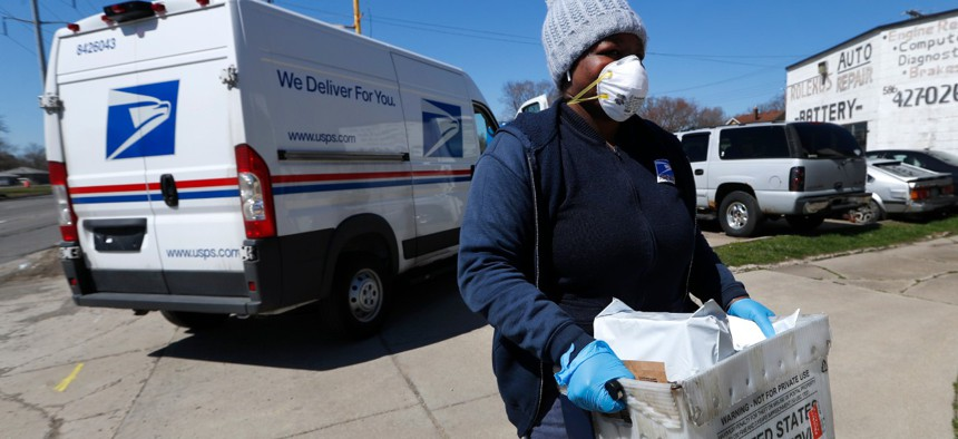 A U.S. Postal worker makes a delivery with gloves and a mask in Warren, Mich., Thursday, April 2.