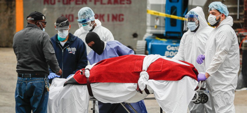 Medical workers in New York City transfer a body to a hearse for removal to a mortuary on March 31.