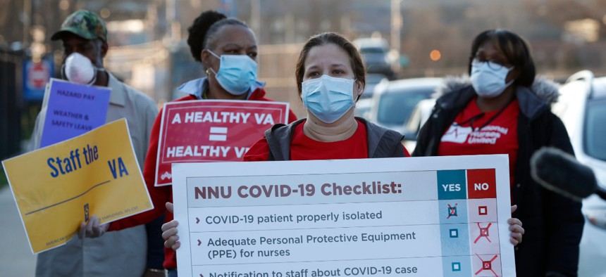 Medical and other VA employees join registered nurses outside New York's Brooklyn VA Medical Center on Monday to call for more personal protective equipment and staffing assistance.
