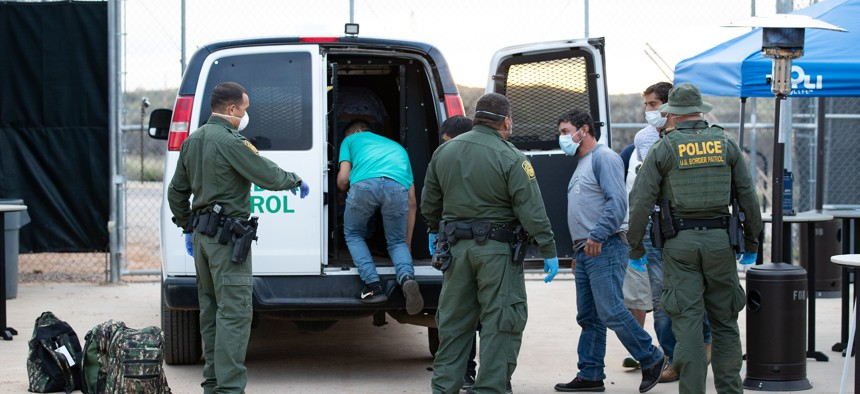 Border Patrol agents use personal protective equipment as they prepare to transport a group of individuals encountered near Sasabe, Ariz. in March.