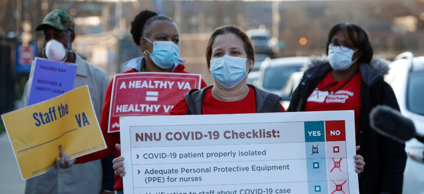 Nurses and other staff outside the Brooklyn Veterans Administration Medical Center on April 6 in New York to call for more personal protective equipment and staffing assistance to care for COVID-19 patients.