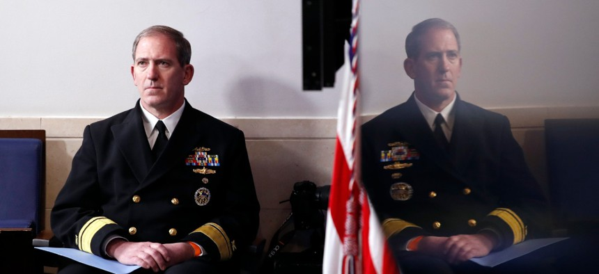 Navy Rear Adm. John Polowczyk, supply chain task force lead at FEMA, listens as President Trump speaks at the White House on April 13 about the government's response to the COVID-19 pandemic.