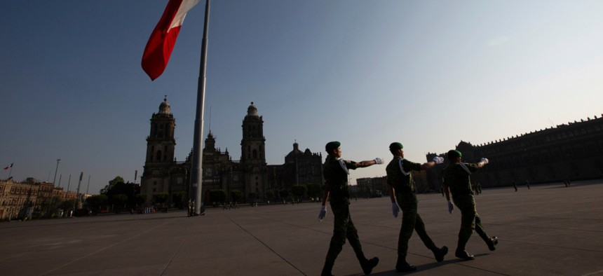 Mexican soldiers leave the Zocalo square after deploying the national flag in Mexico City in March.