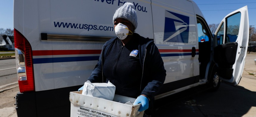 A U.S. Postal Service worker makes a delivery with gloves and a mask in Warren, Mich., in early April.