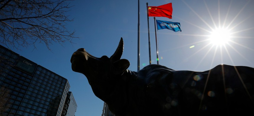 A delivery worker rides his cart by the investment icon bull statue on display outside a bank in Beijing in March.