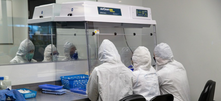 Workers at Aria Diagnostics assemble COVID-19 tests in Indianapolis on Thursday.
