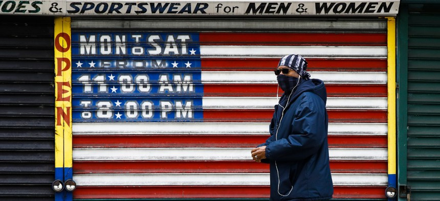 A person wearing a protective face mask as a precaution against the coronavirus walks past a shuttered business in Philadelphia, Thursday, April 23, 2020.
