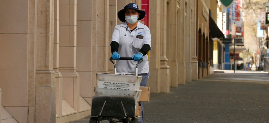 Postal carrier Jasmine Yang wears a mask and gloves as preventative measures against the coronavirus, as she delivers the mail in Sacramento on March 25.