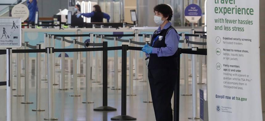A worker wears a mask while standing near a TSA precheck entrance in a terminal at San Francisco International Airport.