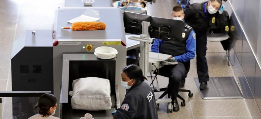 TSA agents wear masks as they screen passengers at Seattle-Tacoma International Airport on April 15.