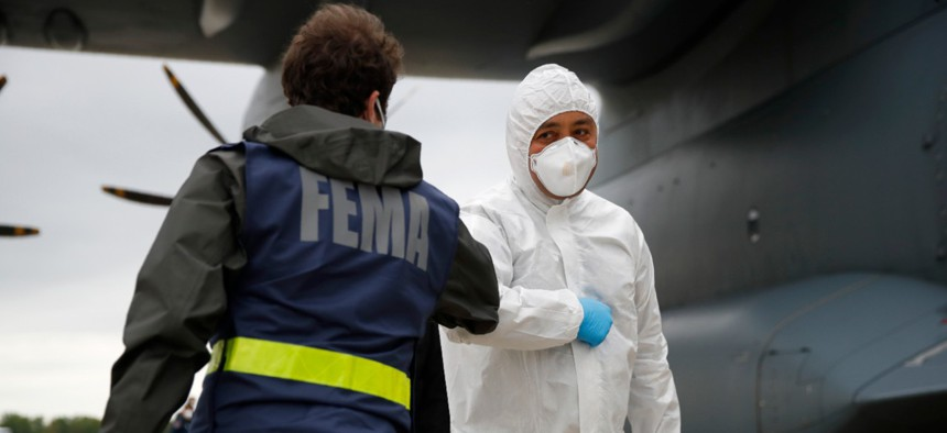 A Turkish military flight crew member, right, bumps elbows with a FEMA worker as crews unload a donation of medical supplies from Turkey on April 28.