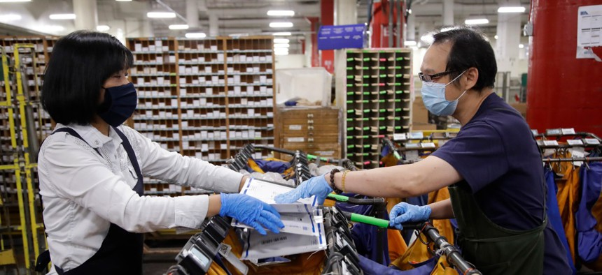 Postal workers May Chen, left, and Wilson Yu wear masks and gloves during the coronavirus pandemic as they sort mail at the United States Postal Service processing and distribution center on April 30 in Oakland, Calif.