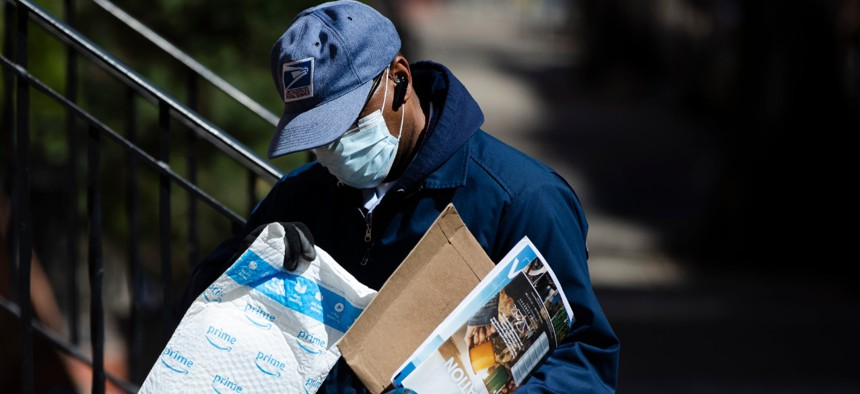 A U.S. Postal Service worker makes a delivery with gloves and a mask in Philadelphia on April 2.