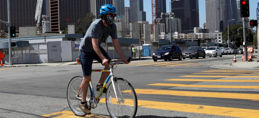 A cyclist covers his face with a mask Thursday, May 14, 2020, in Los Angeles.