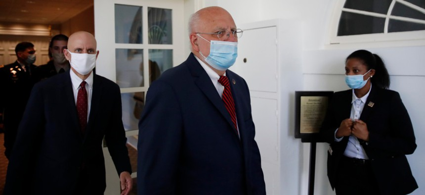 Dr. Robert Redfield, director of the Centers for Disease Control and Prevention, center, arrives for a May 15 press conference on the coronavirus pandemic.