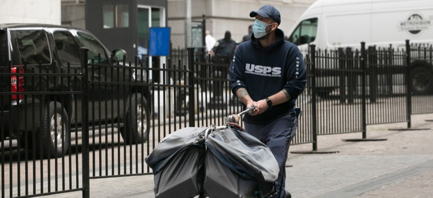 A masked postal worker makes his rounds on May 26 in New York during the coronavirus pandemic.