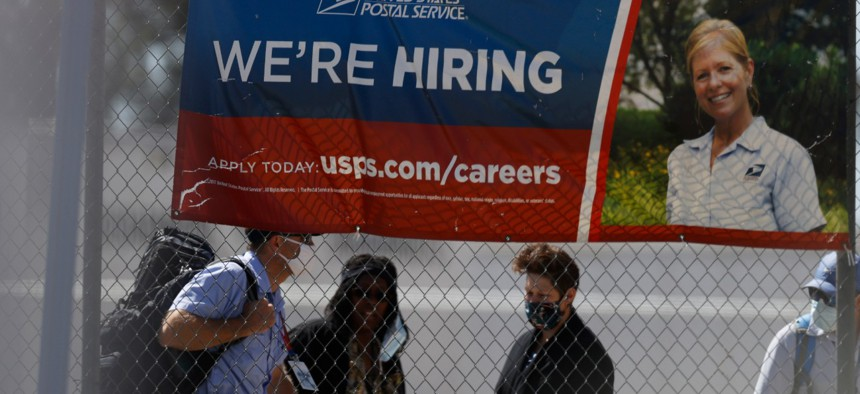 Employees meet outside the U.S. Postal Service distribution facility on Friday, May 22, 2020, in east Denver.