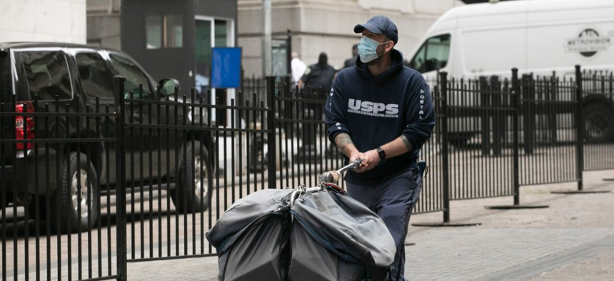 A masked postal worker pushes a cart of mail as he makes his rounds, Tuesday, May 26, 2020, in New York.