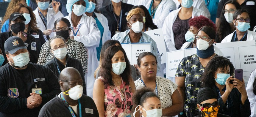 Health care workers at Brooklyn's Kings County Hospital show their solidarity with the Black Lives Matter movement on June 4 in New York during the coronavirus pandemic.