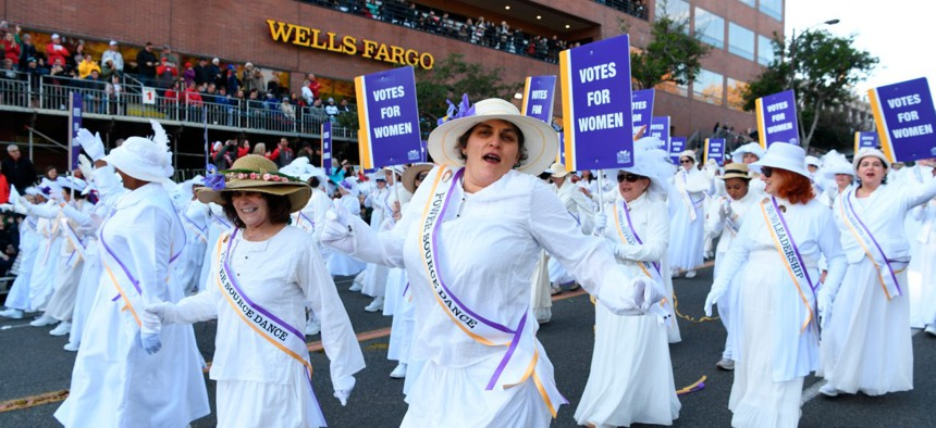 Women portraying suffragettes walk with the Pasadena Celebrates 2020 float at the 131st Rose Parade in Pasadena, California, Wednesday, Jan. 1, 2020.