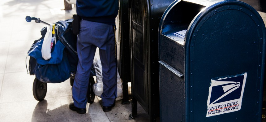 A USPS worker is shown emptying the mailbox on a Manhattan street in 2012.