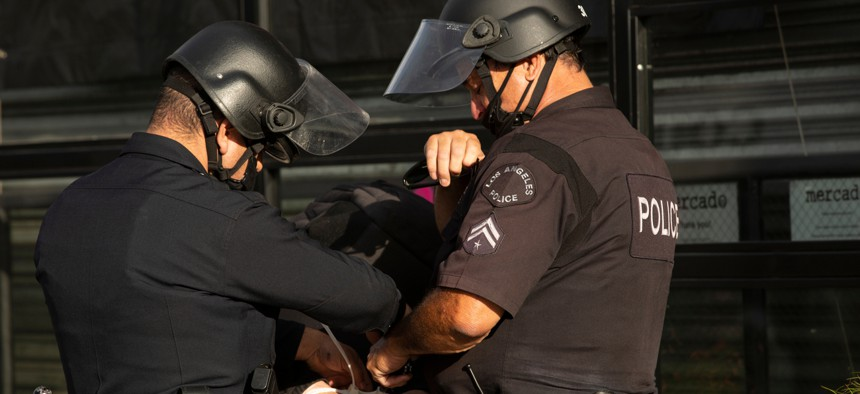 An individual protesting the killing of George Floyd is apprehended by Los Angeles police officers in May.