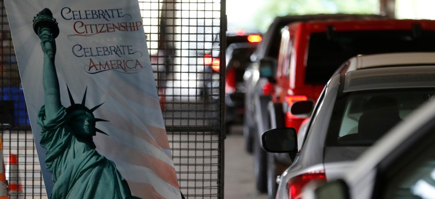 Cars line up during a drive-thru naturalization service in a parking structure at the USCIS headquarters on Detroit's east side. The ceremony is a way to continue working as the federal courthouse is shut down due to coronavirus.