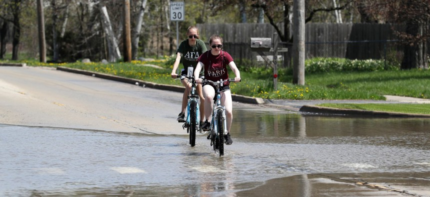 People ride bicycles on a flooded road in Waukegan, Illinois, north of Chicago