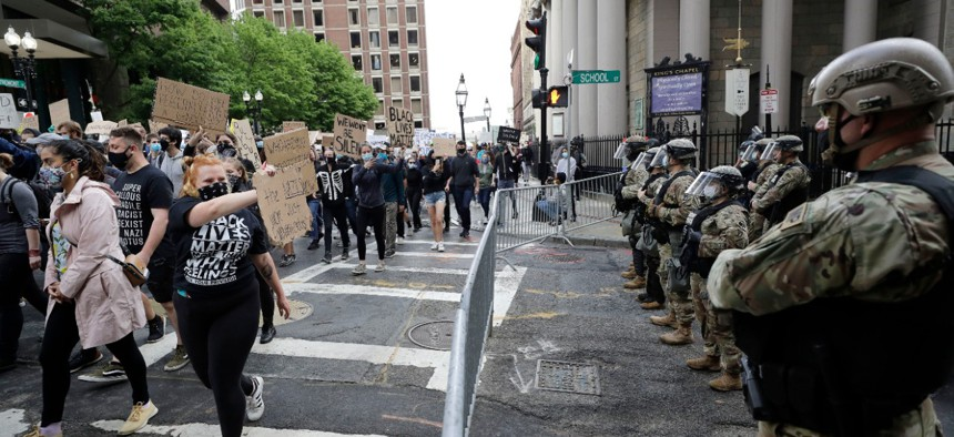 People carry placards, left, as they march past soldiers from the Massachusetts National Guard, right, during a protest against police brutality on June 7.