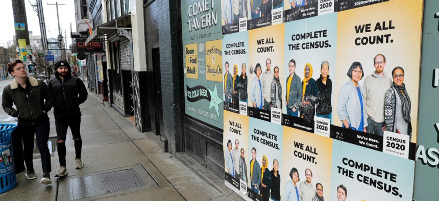 People walk past posters encouraging participation in the 2020 Census, Wednesday, April 1, 2020, in Seattle's Capitol Hill neighborhood.