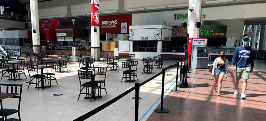 People walk past the nearly empty food court at Providence Place shopping mall, Monday, June 1 in Rhode Island.