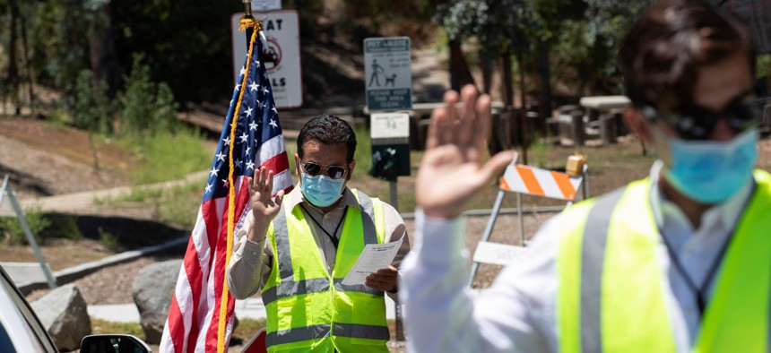 Immigration service officers lead an oath during a drive-in citizenship ceremony in El Cajon, Calif., on June 26.