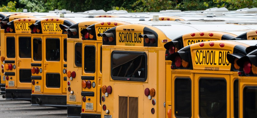 Fairfax County Public School buses are lined up at a maintenance facility in Lorton, Va., on July 24. The nation's 10th largest school district plans an all-virtual start to the fall semester.