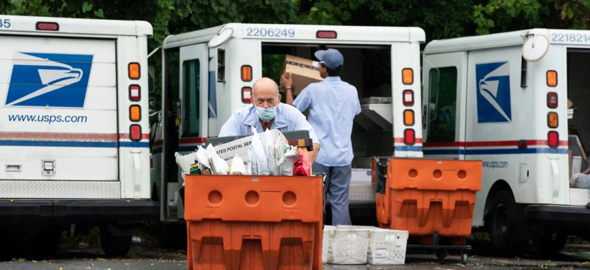 Letter carriers load mail trucks for deliveries at a U.S. Postal Service facility in McLean, Va., on July 31.