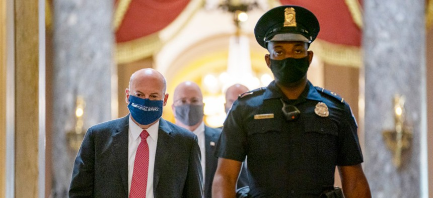 Postmaster General Louis DeJoy, left, is escorted to House Speaker Nancy Pelosi's office on Capitol Hill in Washington, Wednesday, Aug. 5, 2020.