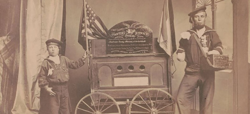 Bernard Tobey, a double amputee, and his son, wearing Union sailor uniforms, standing beside a small wagon displaying Secretary of War Edwin Stanton's dispatch on the fall of Fort Fisher.
